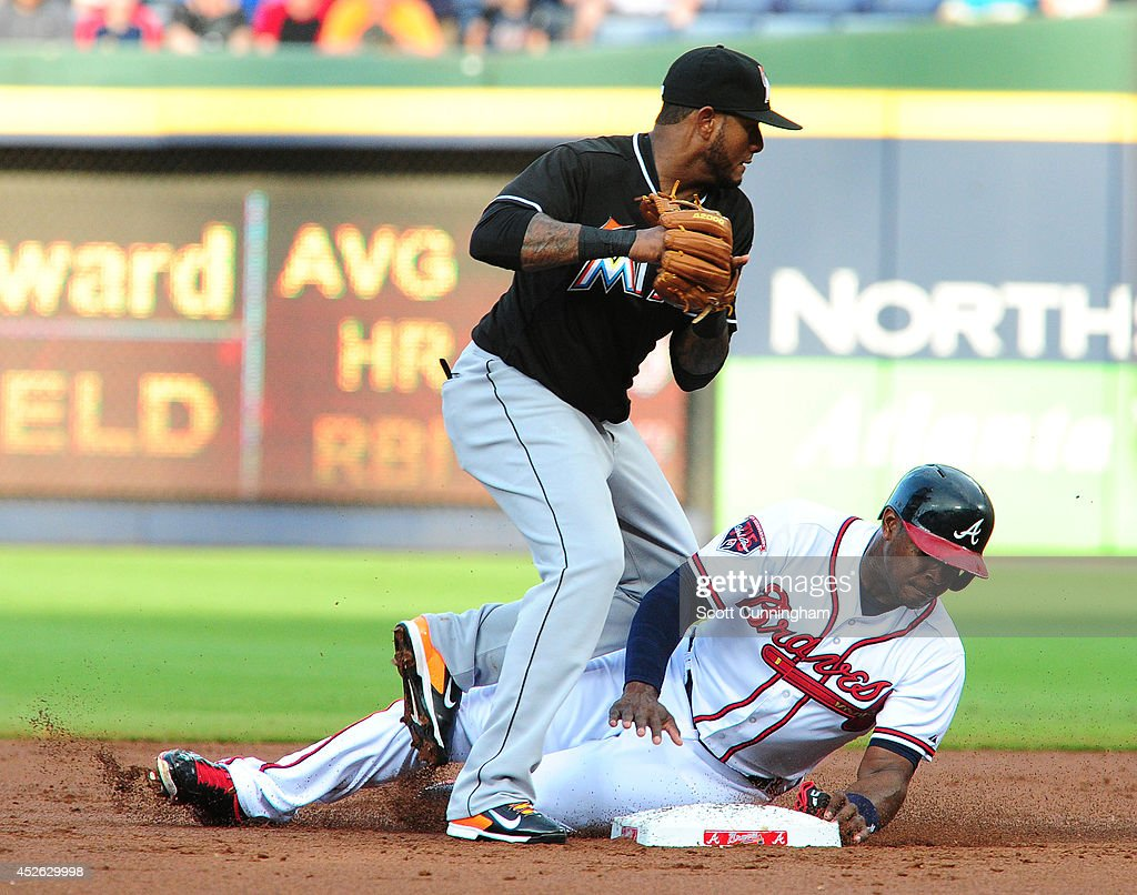 Justin Upton #8 of the Atlanta Braves breaks up a double play attempt by Jordany Valdespin #1 of the Miami Marlins during the second inning at Turner Field on July 24, 2014 in Atlanta, Georgia.