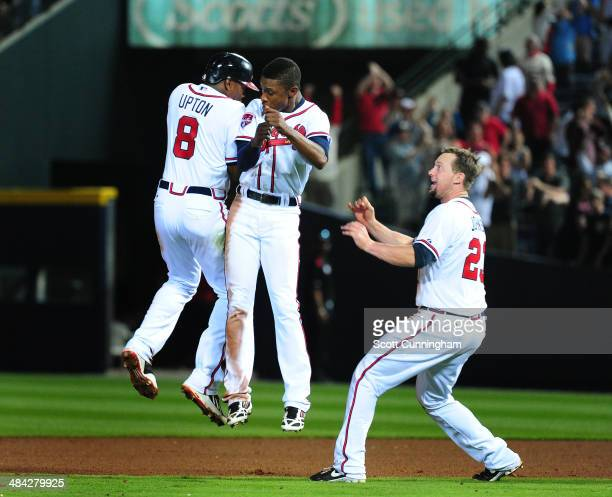 Justin Upton of the Atlanta Braves is congratulated by B J Upton and Chris Johnson after knocking in the game winning run in the 10th inning against...