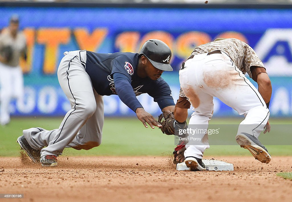Justin Upton #8 of the Atlanta Braves is tagged out by Everth Cabrera #2 of the San Diego Padres on a steal attempt at second base during the eighth inning of a baseball game at Petco Park August 3, 2014 in San Diego, California.