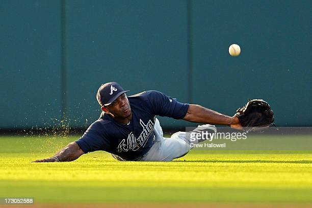 Justin Upton of the Atlanta Braves makes an unsuccessful dive for a catch on a double hit by Ben Revere of the Philadelphia Phillies in the second...