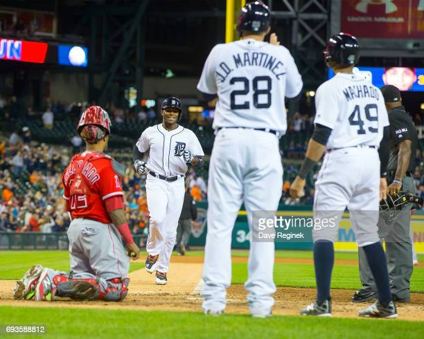 Justin Upton of the Detroit Tigers heads towards home plate after hitting his eighth inning home run to drive in teammates Nicholas Castellanos and...