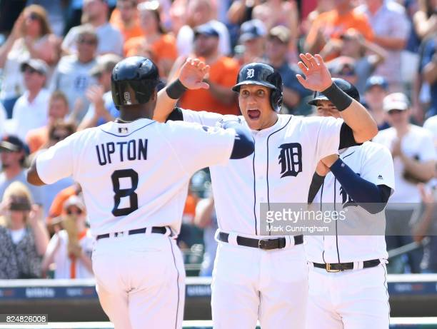 Justin Upton of the Detroit Tigers is greeted at home plate by teammate Mikie Mahtook after hitting a grand slam home run during the game against the...