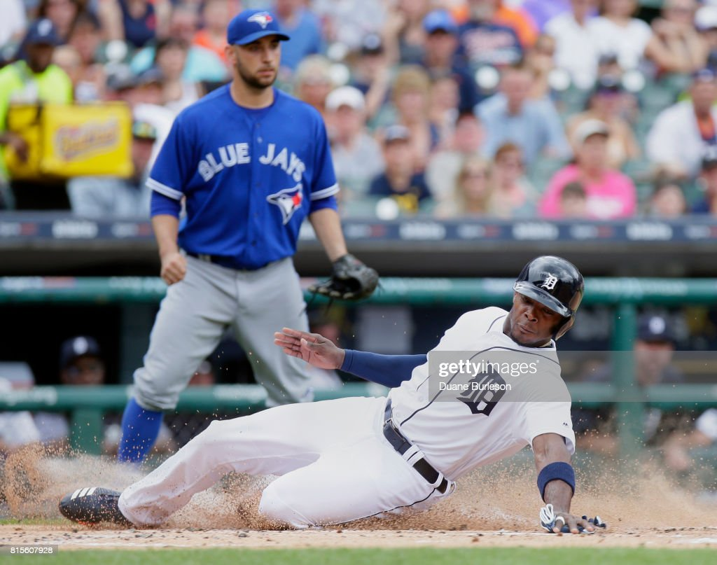 Justin Upton #8 of the Detroit Tigers scores from third base on a sacrifice fly ball hit by J.D. Martinez of the Detroit Tigers as pitcher Marco Estrada #25 of the Toronto Blue Jays backs up at home plate during the first inning at Comerica Park on July 16, 2017 in Detroit, Michigan.