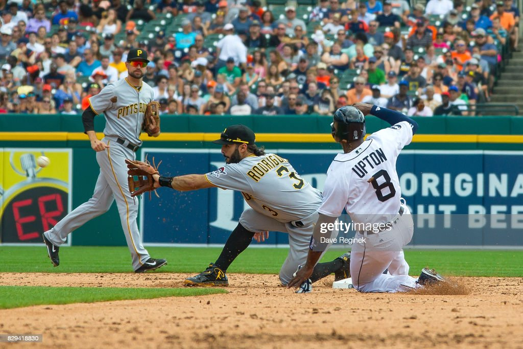 Justin Upton #8 of the Detroit Tigers slides into second base on a wild pitch and beats the throw to Sean Rodriguez #3 of the Pittsburgh Pirates in the third inning during a MLB game at Comerica Park on August 10, 2017 in Detroit, Michigan. The Pirates defeated the Tigers 7-5.