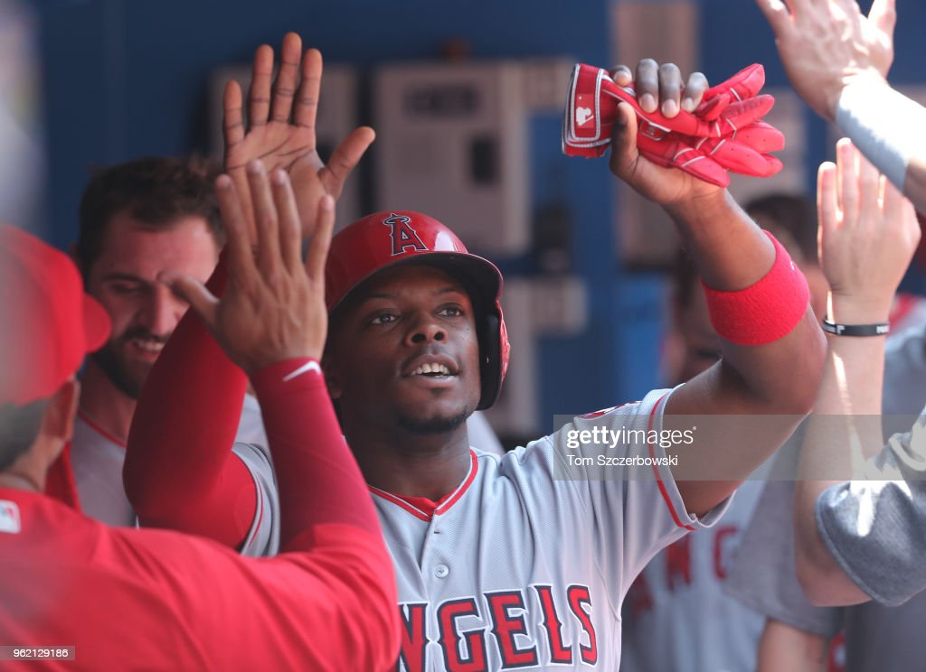 Justin Upton #8 of the Los Angeles Angels of Anaheim is congratulated by teammates in the dugout after scoring a run in the third inning during MLB game action against the Toronto Blue Jays at Rogers Centre on May 24, 2018 in Toronto, Canada.