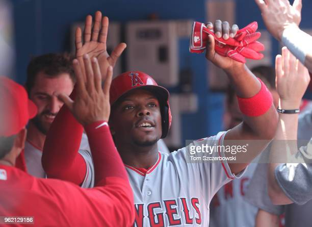 Justin Upton of the Los Angeles Angels of Anaheim is congratulated by teammates in the dugout after scoring a run in the third inning during MLB game...