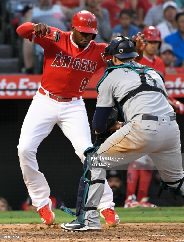 Justin Upton #8 of the Los Angeles Angels of Anaheim is tagged out at home by Mike Zunino #3 of the Seattle Mariners in the fifth inning at Angel Stadium on July 28, 2018 in Anaheim, California.