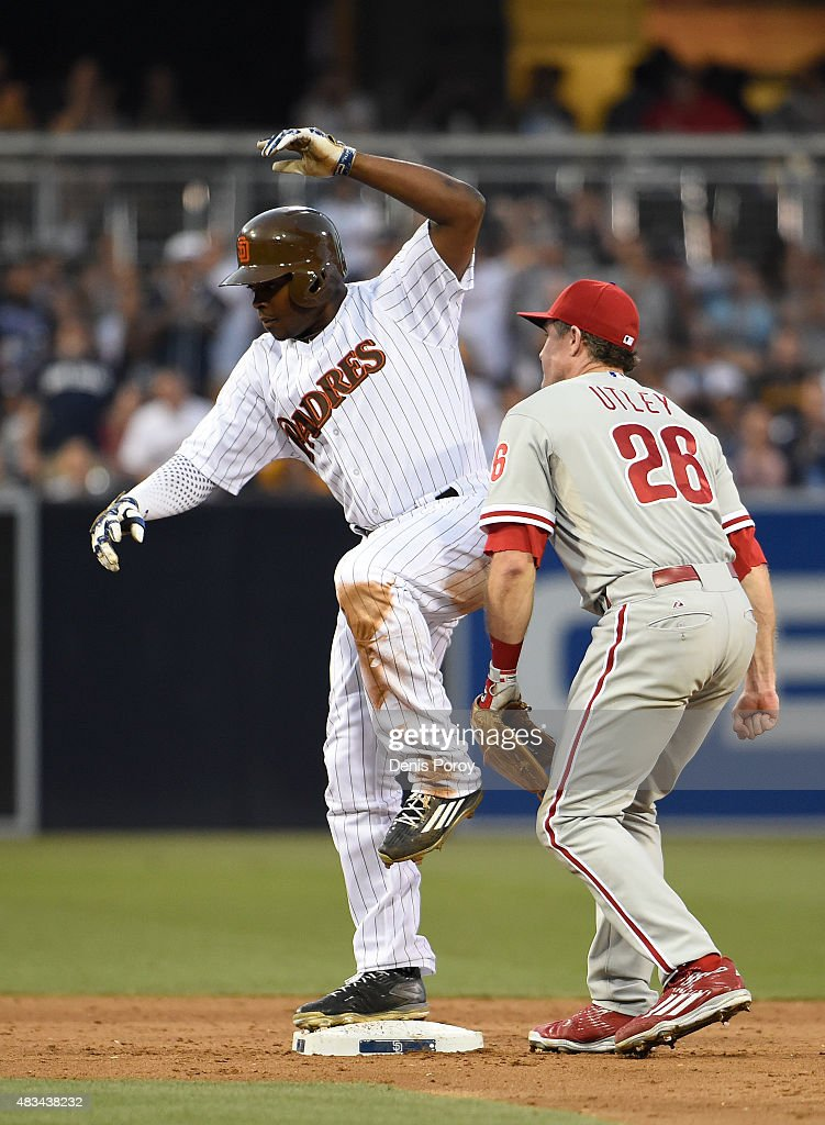 Justin Upton #10 of the San Diego Padres balances on second base as Chase Utley #26 of the Philadelphia Phillies loses the ball during the sixth inning of a baseball game at Petco Park August 8, 2015 in San Diego, California.