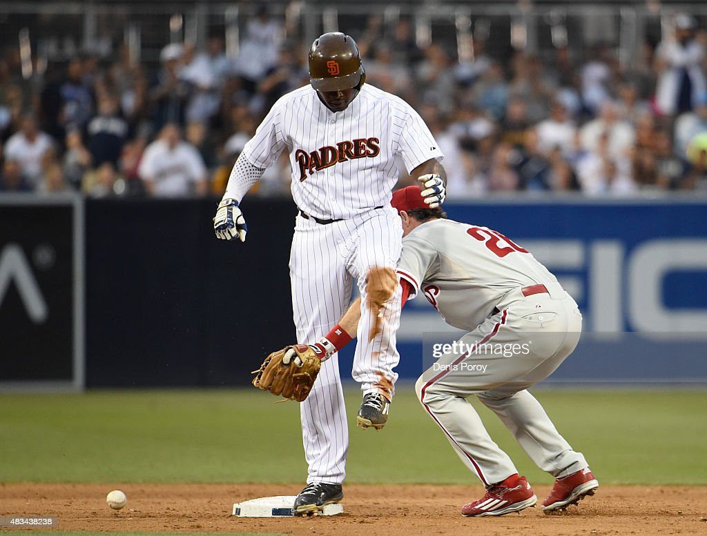Justin Upton #10 of the San Diego Padres is safe on second base as Chase Utley #26 of the Philadelphia Phillies loses the ball during the sixth inning of a baseball game at Petco Park August 8, 2015 in San Diego, California.