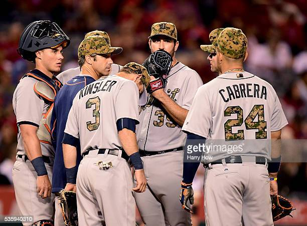Justin Verlander of the Detroit Tigers meets with teammates on the mound during the eighth inning against the Los Angeles Angels at Angel Stadium of...