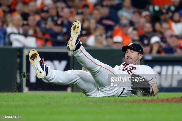 Justin Verlander of the Houston Astros fails to field a ground ball against the Washington Nationals during the fourth inning in Game Two of the 2019...