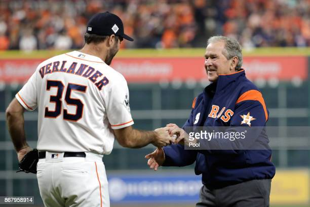 Justin Verlander of the Houston Astros speaks with George W Bush after throwing out the ceremonial first pitch before game five of the 2017 World...