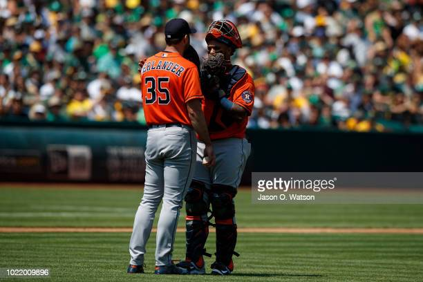 Justin Verlander of the Houston Astros talks to Martin Maldonado during a mound visit during the third inning against the Oakland Athletics at the...