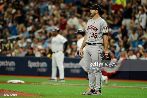 Justin Verlander of the Houston Astros watches a homer as Austin Meadows of the Tampa Bay Rays rounds first base in the first inning during Opening...