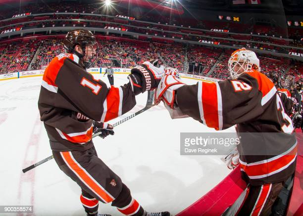 Justin Wells of the Bowling Green Falcons pounds gloves with teammate Brett Rich after his first period goal against the Michigan Wolverines during...