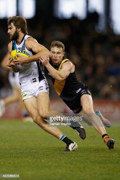 Justin Westhoff of the Power is tackled by Nathan Foley of the Tigers during the round 17 AFL match between the Richmond Tigers and the Port Adelaide...