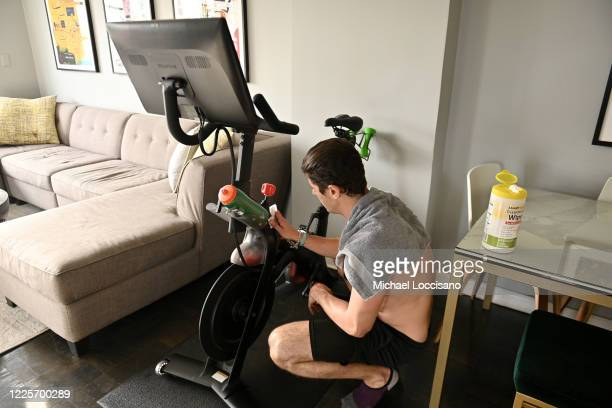 Justin Wiezel works out on a Peloton high-tech stationary bike in his apartment on May 18, 2020 in New York City. Coronavirus temporarily shut down...