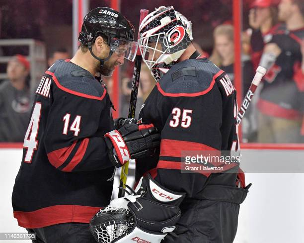 Justin Williams and Curtis McElhinney of the Carolina Hurricanes celebrate after a win against the New York Islanders in Game Three of the Eastern...