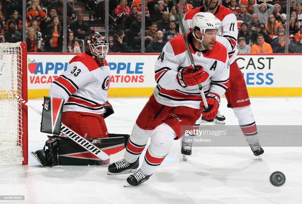 Justin Williams #14 and Scott Darling #33 of the Carolina Hurricanes react to the airborne puck against the Philadelphia Flyers on April 5, 2018 at the Wells Fargo Center in Philadelphia, Pennsylvania.