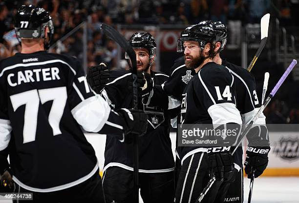Justin Williams, Jeff Carter and Jarret Stoll of the Los Angeles Kings celebrate a goal scored by teammate Willie Mitchell in the second period of...