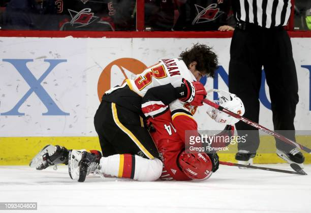 Justin Williams of the Carolina Hurricanes and Sean Monahan of the Calgary Flames get tangled up behind the net during an NHL game on February 3,...