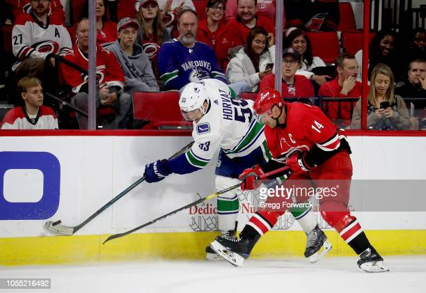 Justin Williams of the Carolina Hurricanes battles for a puck along the boards with Bo Horvat of the Vancouver Canucks during an NHL game on October...
