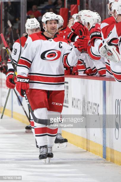 Justin Williams of the Carolina Hurricanes celebrates his third period goal against the Ottawa Senators with teammates at the players bench at...