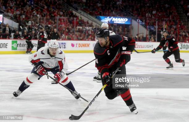 Justin Williams of the Carolina Hurricanes controls the puck and drives the net as Dmitry Orlov of the Washington Capitals defends in Game Four of...