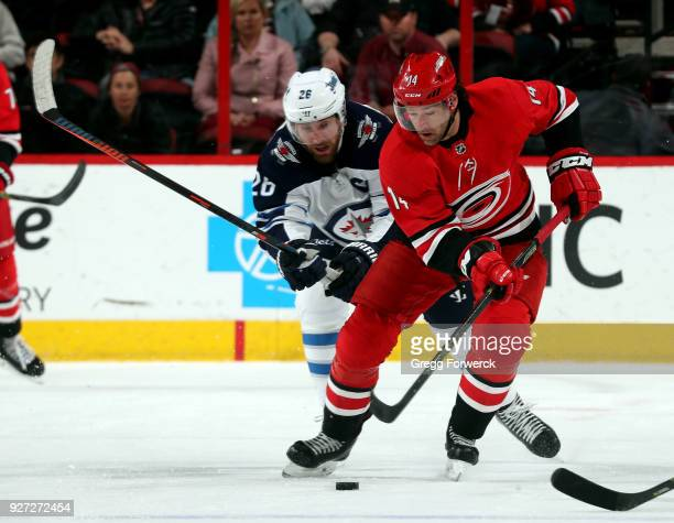 Justin Williams of the Carolina Hurricanes controls the puck while stick checked by Blake Wheeler of the Winnipeg Jets during an NHL game on March 4...