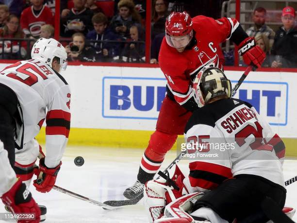 Justin Williams of the Carolina Hurricanes has his shot turned away by goaltender Cory Schneider and Mirco Mueller of the New Jersey Devils during an...