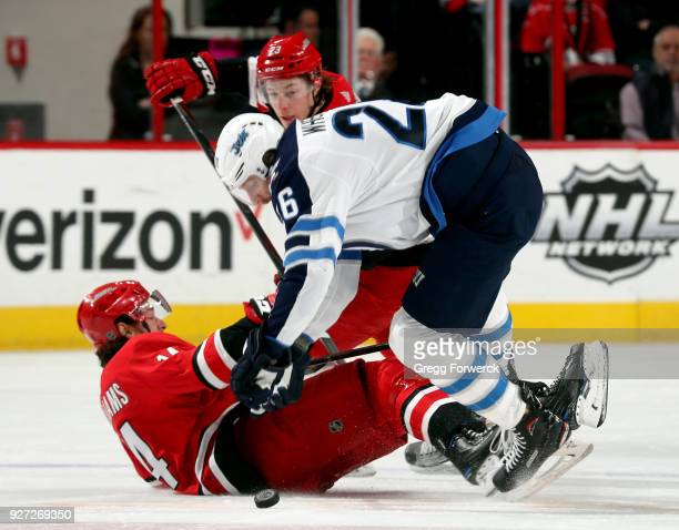 Justin Williams of the Carolina Hurricanes is checked by Blake Wheeler of the Winnipeg Jets during an NHL game on March 4 2018 at PNC Arena in...