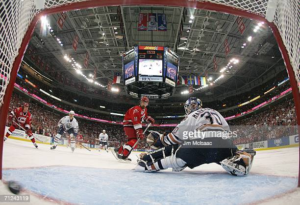 Justin Williams of the Carolina Hurricanes looks on as goaltender Jussi Markkanen of the Edmonton Oilers fails to stop the second goal by Frantisek...