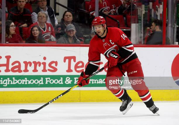 Justin Williams of the Carolina Hurricanes looks to pass the puck during an NHL game against the Minnesota Wild on March 23, 2019 at PNC Arena in...