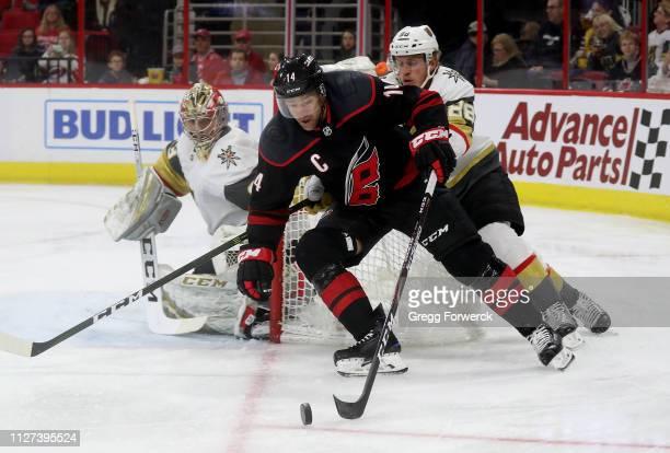 Justin Williams of the Carolina Hurricanes plays the puck near the crease as Nate Schmidt of the Vegas Golden Knights defends and goaltender Maxime...