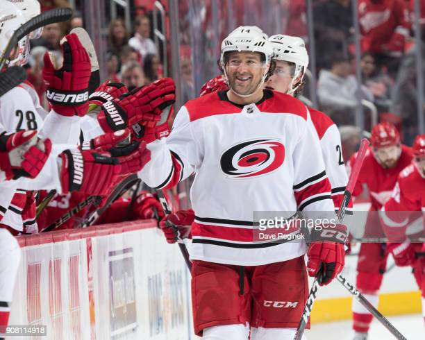 Justin Williams of the Carolina Hurricanes pounds gloves with teammates on the bench following his third period goal during an NHL game against the...