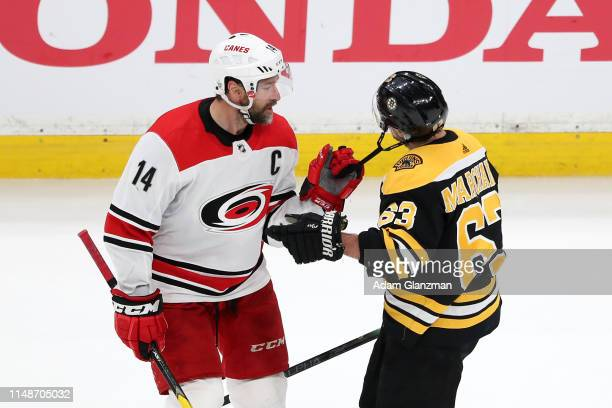 Justin Williams of the Carolina Hurricanes pulls on the chinstrap of Brad Marchand of the Boston Bruins during the second period in Game Two of the...