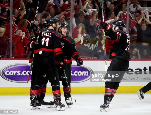 Justin Williams of the Carolina Hurricanes scores a goal on an assist by Brett Pesce and celebrates with teammates Jordan Staal and Brock McGinn in...