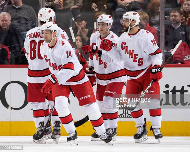 Justin Williams of the Carolina Hurricanes skates to the bench after celebrating his third period goal with teammates Teuvo Teravainen, Sebastian Aho...
