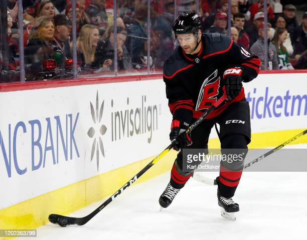 Justin Williams of the Carolina Hurricanes skates with the puck along the boards during an NHL game against the New York Rangers at PNC Arena on...