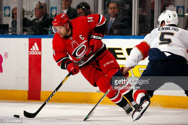 Justin Williams of the Carolina Hurricanes skates with the puck against Aaron Ekblad of the Florida Panthers at the BBT Center on February 21 2019 in...