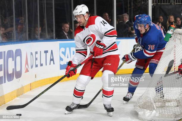 Justin Williams of the Carolina Hurricanes skates with the puck against Brady Skjei of the New York Rangers at Madison Square Garden on March 12 2018...