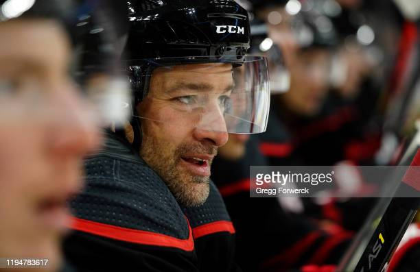 Justin Williams of the Carolina Hurricanes watches action on the ice after his first shift during an NHL game against the New York Islanders on...