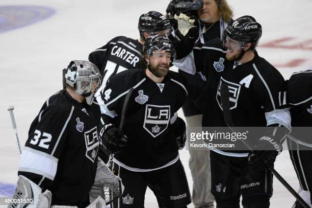 Justin Williams of the Los Angeles Kings celebrates his gamewinning goal in overtime with teammates Jonathan Quick and Anze Kopitar after the Kings...