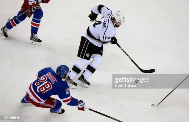 Justin Williams of the Los Angeles Kings controls the puck away from Dominic Moore of the New York Rangers in the first period of Game Four of the...