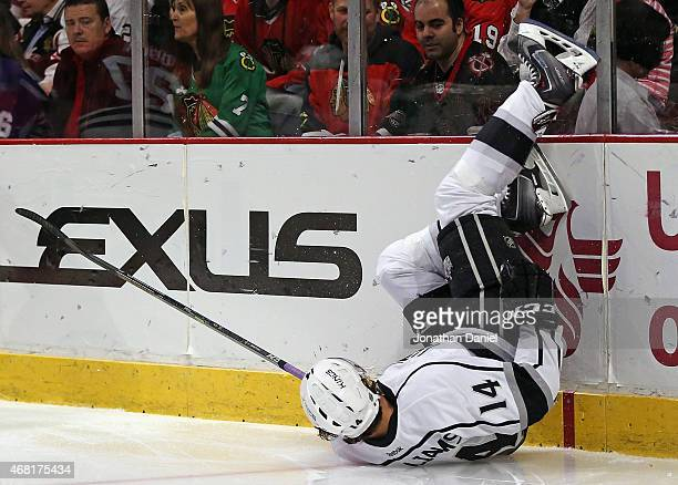 Justin Williams of the Los Angeles Kings hits the boards after loosing control of the puck while slipping against the Chicago Blackhawks at the...