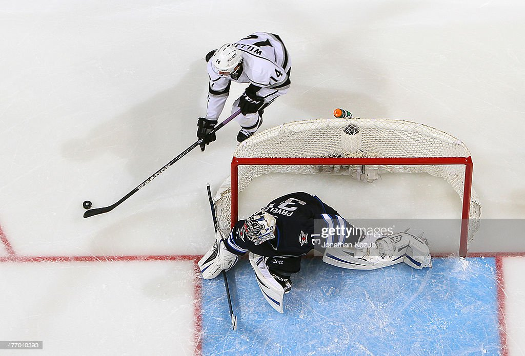 Justin Williams #14 of the Los Angeles Kings plays the puck around the net as goaltender Ondrej Pavelec #31 of the Winnipeg Jets guards the crease during third period action at the MTS Centre on March 6, 2014 in Winnipeg, Manitoba, Canada.