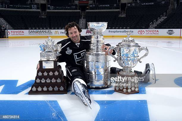 Justin Williams of the Los Angeles Kings poses for a picture with the Stanley Cup Trophy, the Conn Smythe Trophy and the Campbell Cup before the Los...