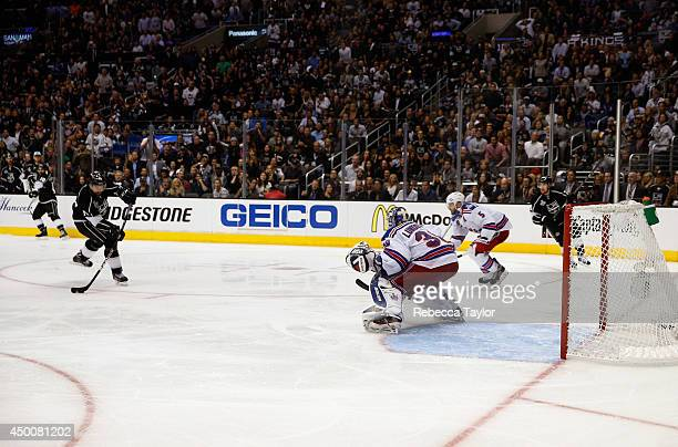 Justin Williams of the Los Angeles Kings shoots and scores the overtime goal on goaltender Henrik Lundqvist of the New York Rangers for the Kings to...