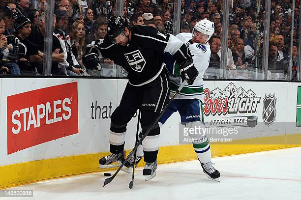 Justin Williams of the Los Angeles Kings skates with the puck against Keith Ballard of the Vancouver Canucks in Game Four of the Western Conference...