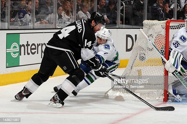 Justin Williams of the Los Angeles Kings skates with the puck against Dan Hamhuis of the Vancouver Canucks in Game Four of the Western Conference...